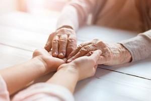 junge und alte Hände abgesichert durch Pflegeversicherung für Studenten