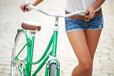 Attraktive Frau mit Fahrrad - Hausratversicherung abgesichert