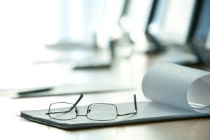 Fakten zur Berufsunfähigkeitsversicherung: Brille auf Schreibtisch