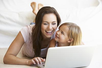 Frau mit Kind vor dem Computer bei der Auswahl der richtigen Zusatzversicherung